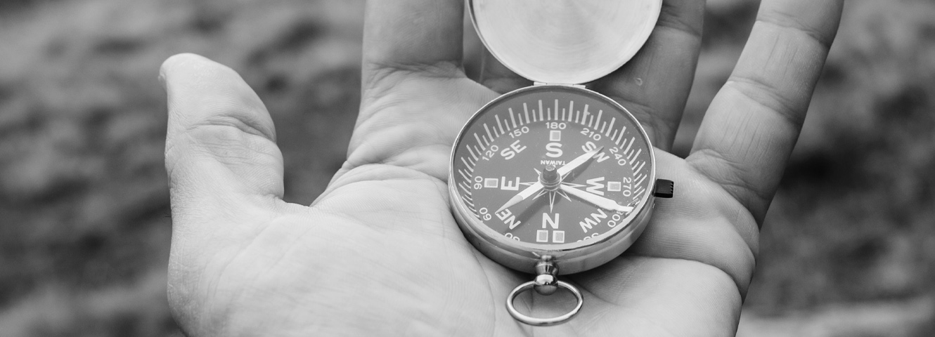 A closely cropped in image of a hand holding a compass.