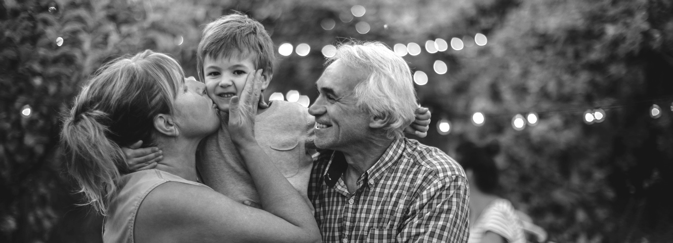 Grandparents hold their grandson. The grandma is kissing the grandson on the cheek.