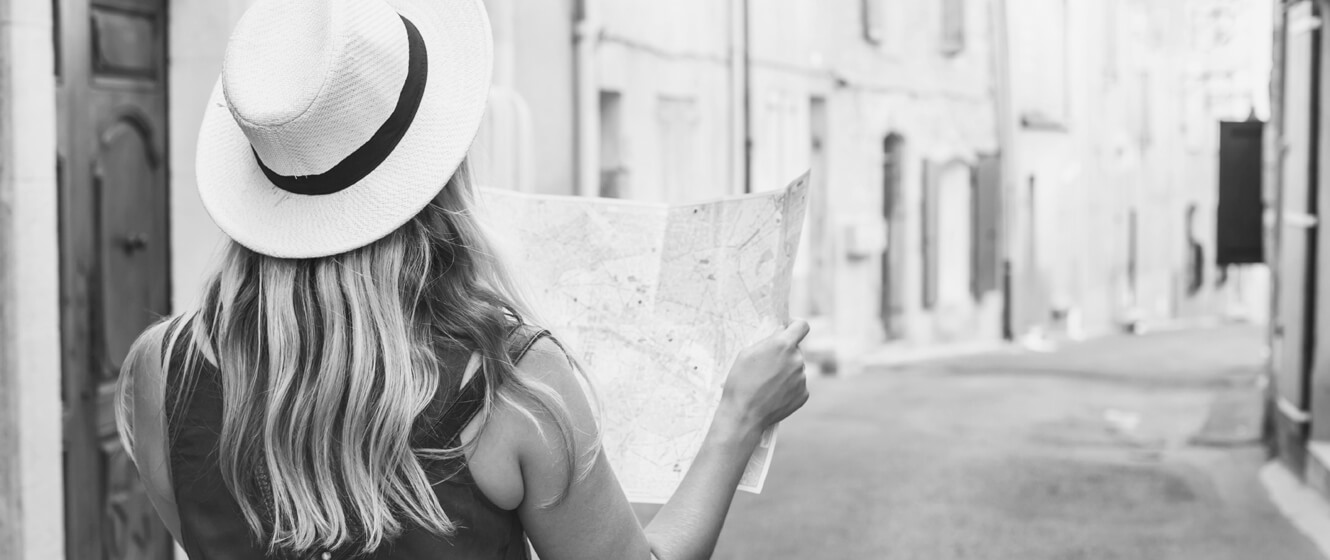 Woman wearing a sun hat and holding a map